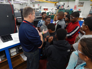 Plouffe Academy students look at tiny parts produced by Accurounds